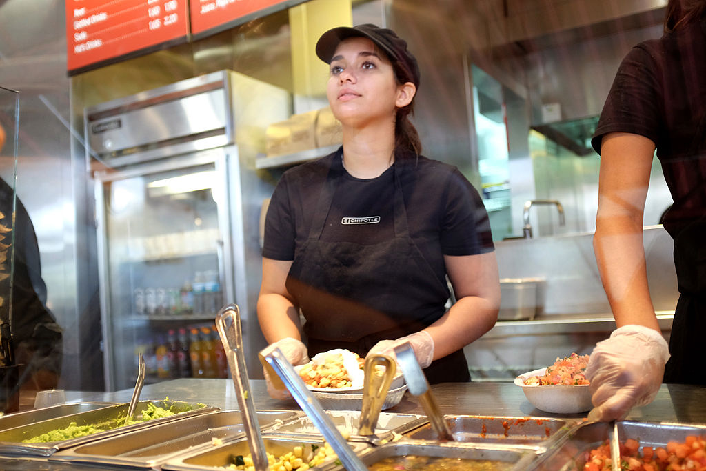 A restaurant worker fills an order at a Chipotle restaurant