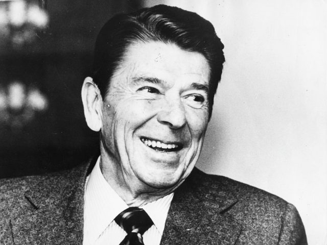 Ronald Reagan smiling while in a suit and tie.