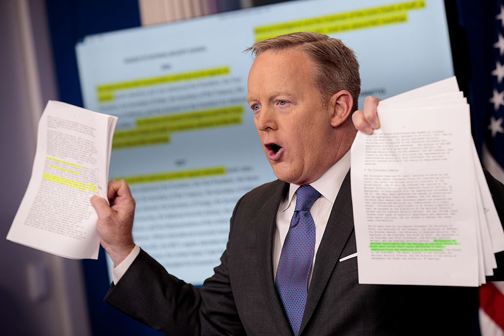 Sean Spicer is talking and holding up two packets of paper.