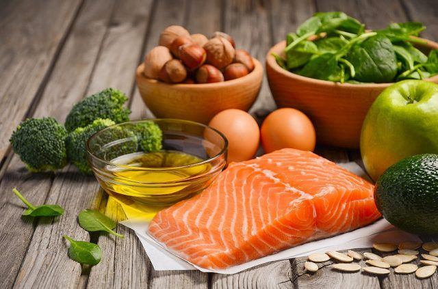 Fish, fruits, nuts, vegetables, and olive oil together on a wooden table.