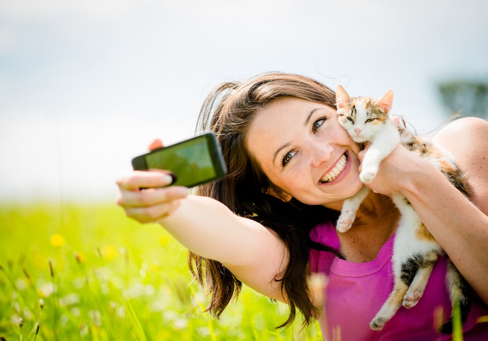A woman takes a selfie with her cat.