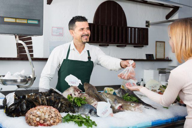A fisherman sells seafood to a customer.