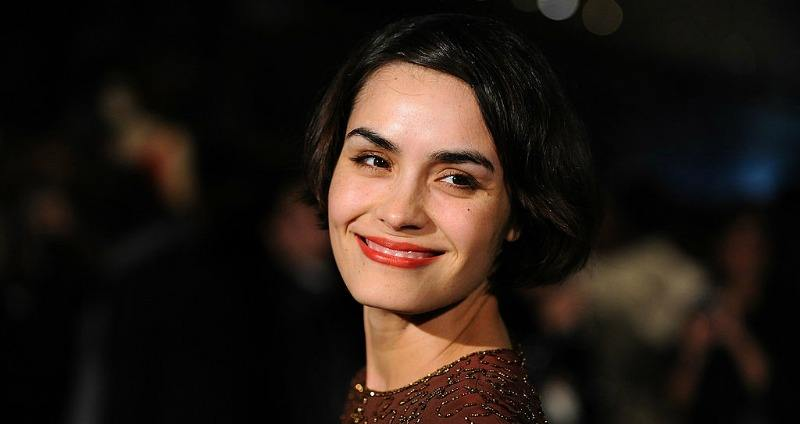 Shannyn Sossamon is smiling and posing on the red carpet.