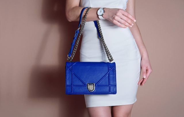 Woman in a white dress holding a blue bag