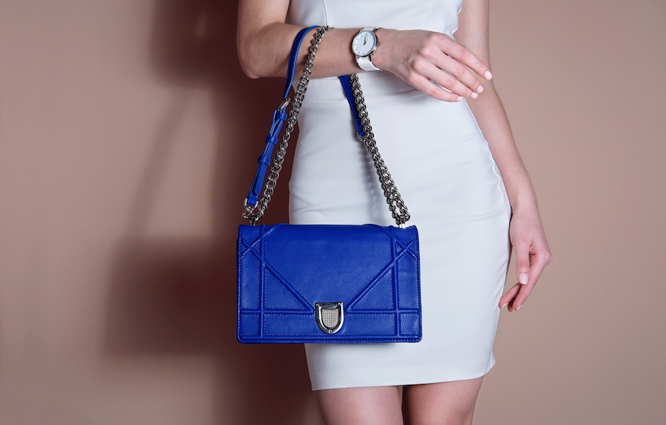 Woman in white dress holding blue bag