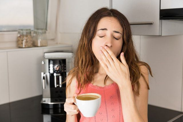 Woman yawning and drinking coffee.