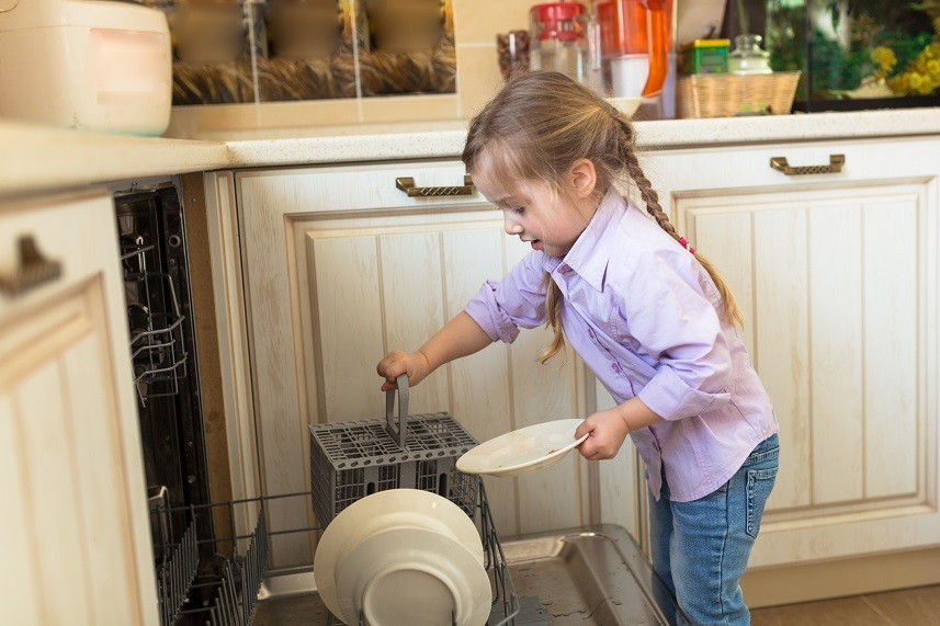 Smiling caucasian girl helping in kitchen