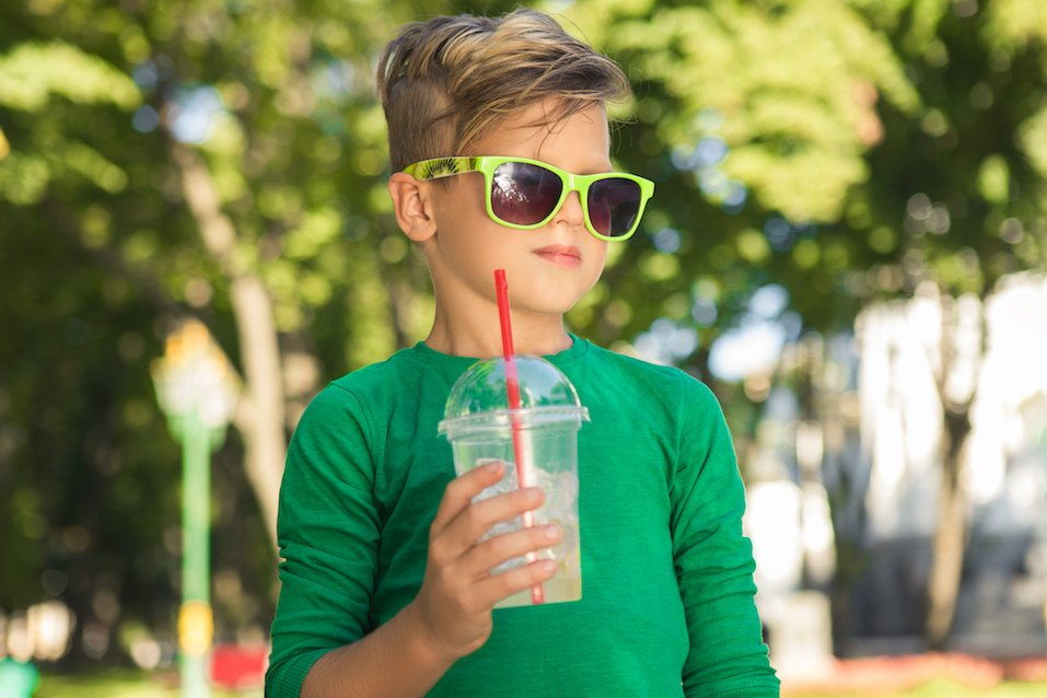 Stylish little Boy holding a cocktail in his hand