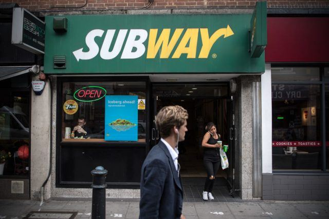 Front view of Subway restaurant building with people walking past