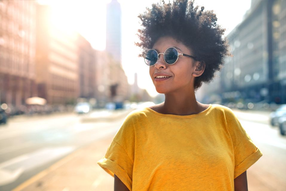 Woman wearing a pair of round sunglasses