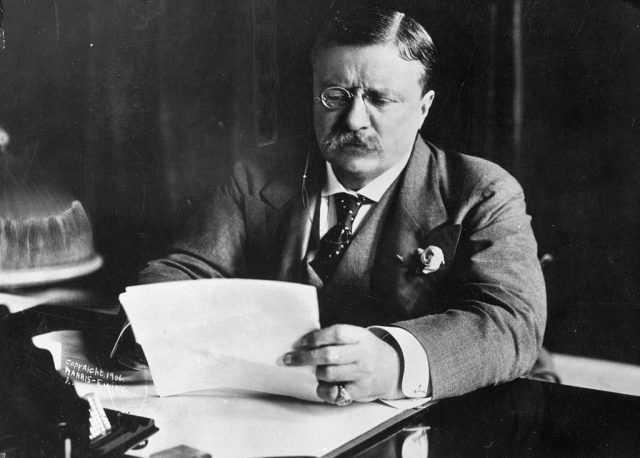 Theodore Roosevelt sits at a desk writing on a piece of paper.