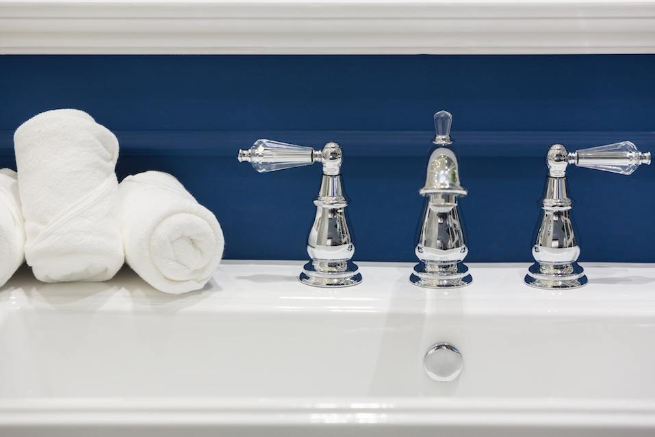 Three white hand towels on a white basin with hot and cold faucets