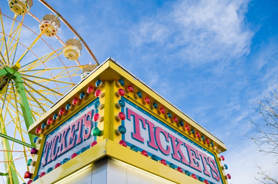 Tickets sign at county fair with Ferris wheel