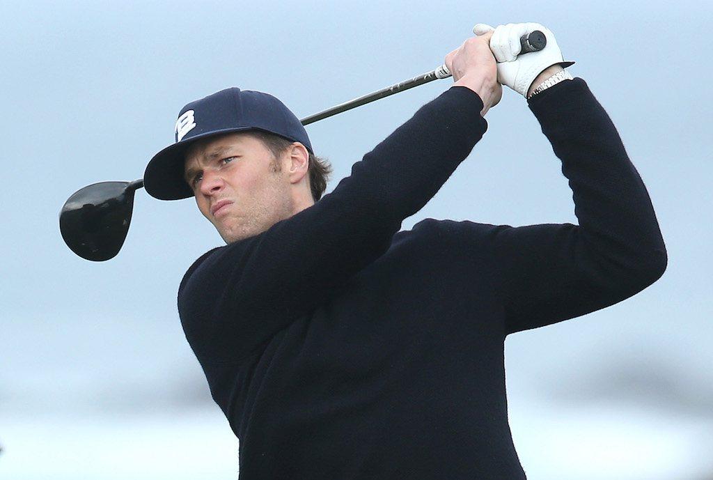 Tom Brady holding a golf club.