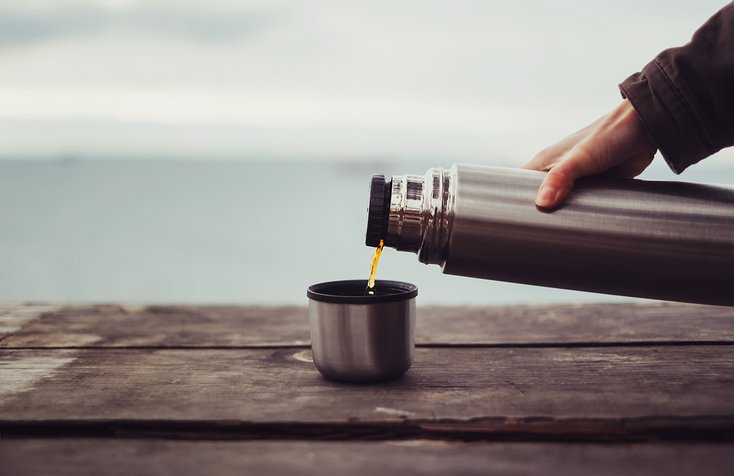 Traveler pouring tea from thermos