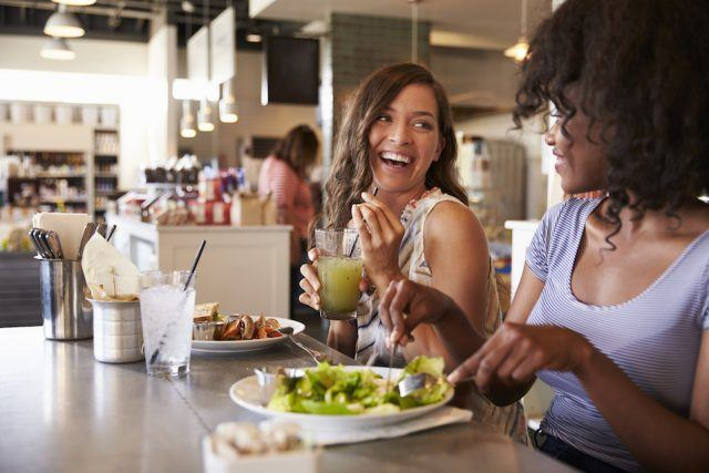 Two women having a good time on a date at a restaurant.