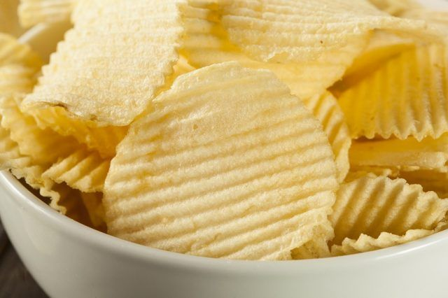Crinkle cut potato chips in a white bowl.