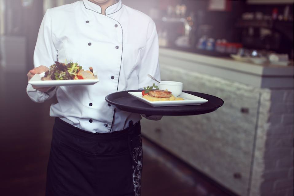Waiters carrying plates with meat dish