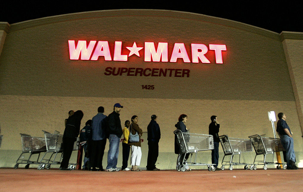 People stand in front of a Walmart store