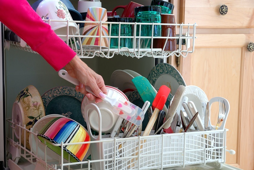 A female hand is shown loading dishes