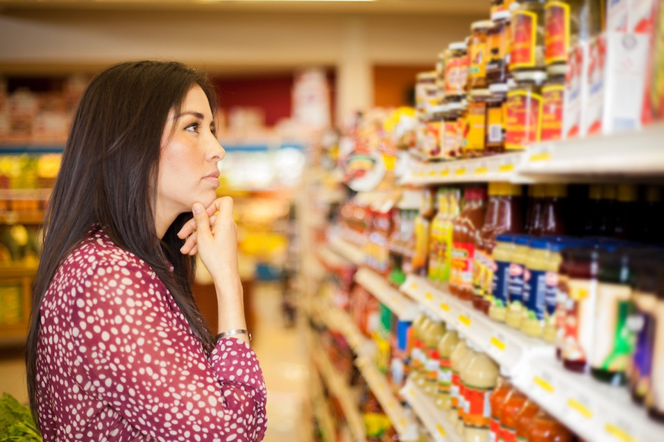 Beautiful brunette looking at some shelves trying to decide what to buy