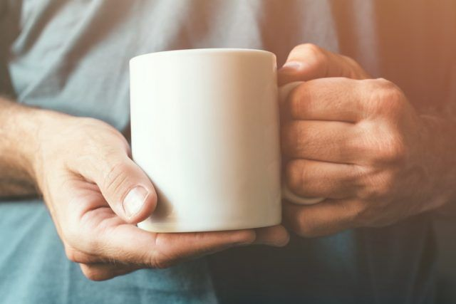 White coffee cup in male hands.