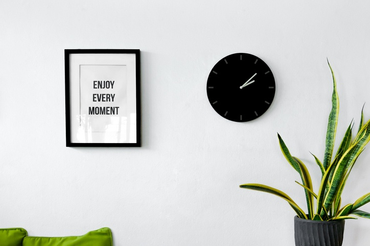White wall decoration with a picture frame, clock and plants