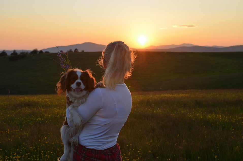 Woman Holding Her Dog in Sunset