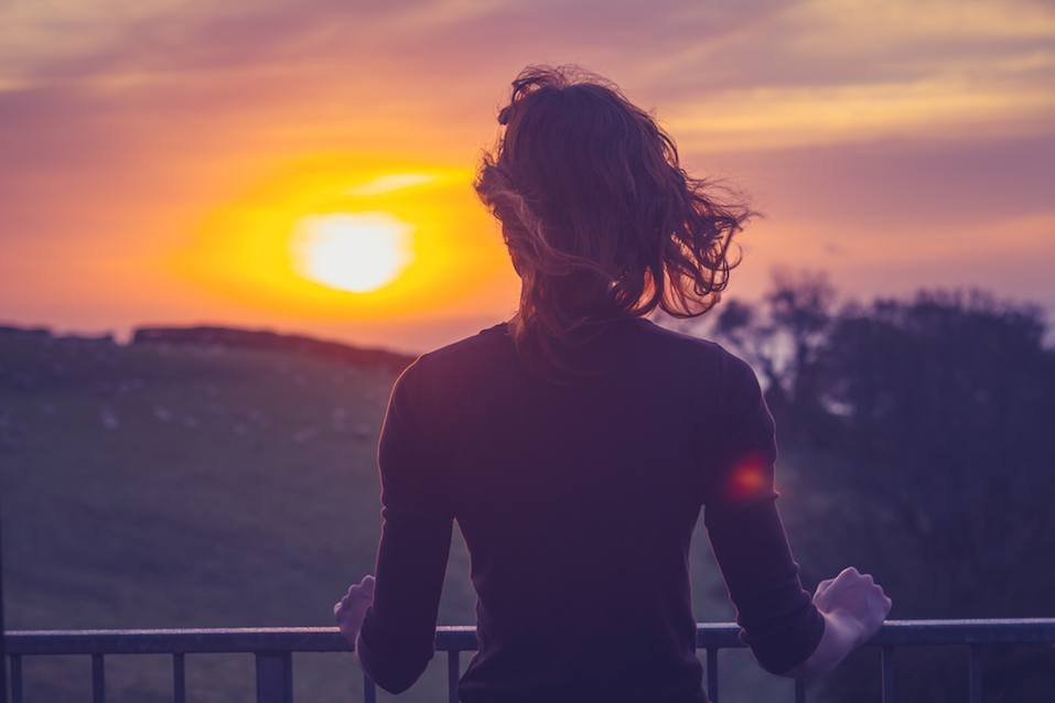 Woman admiring sunset from her balcony
