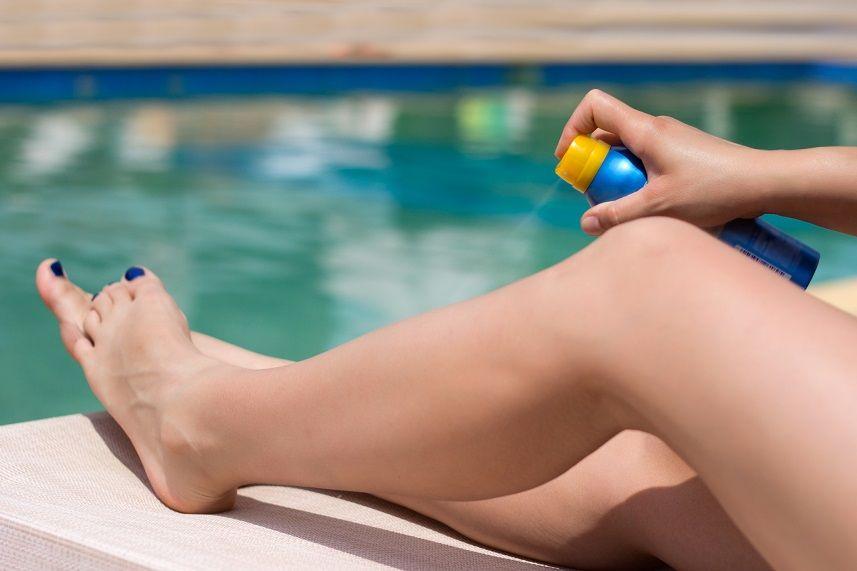 Woman applying suntan spray onto her legs