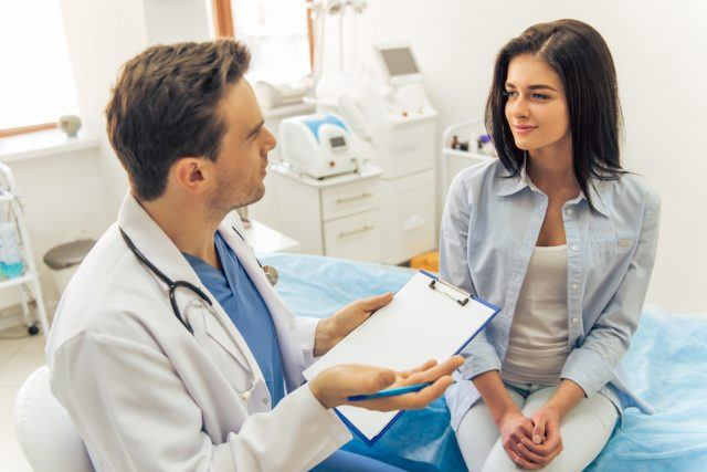 A doctor is talking with young female patient in an office.