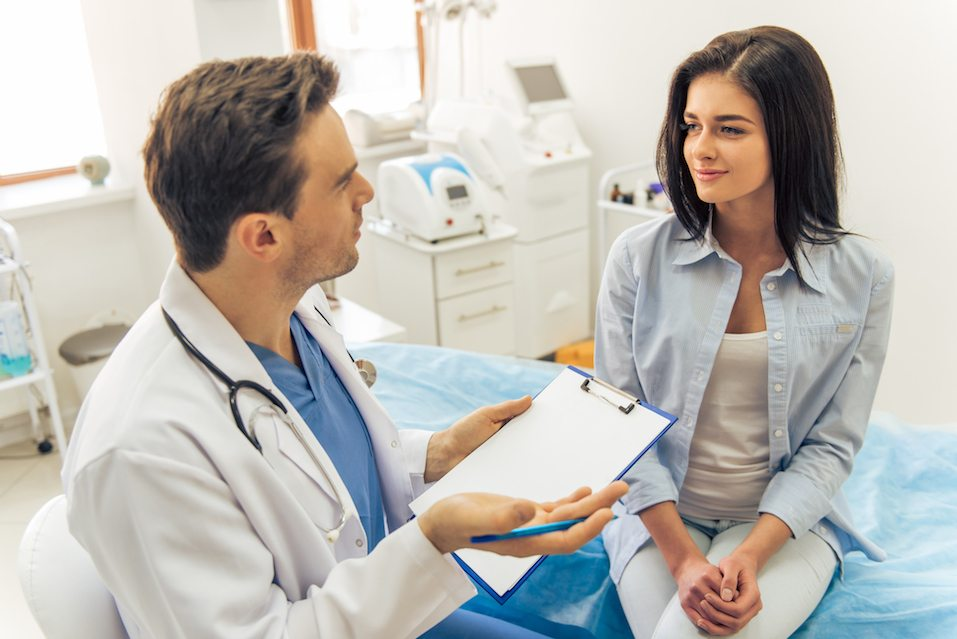 Handsome doctor is talking with young female patient a