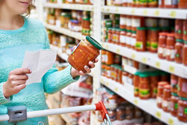 Woman chooses sauce at grocery store.