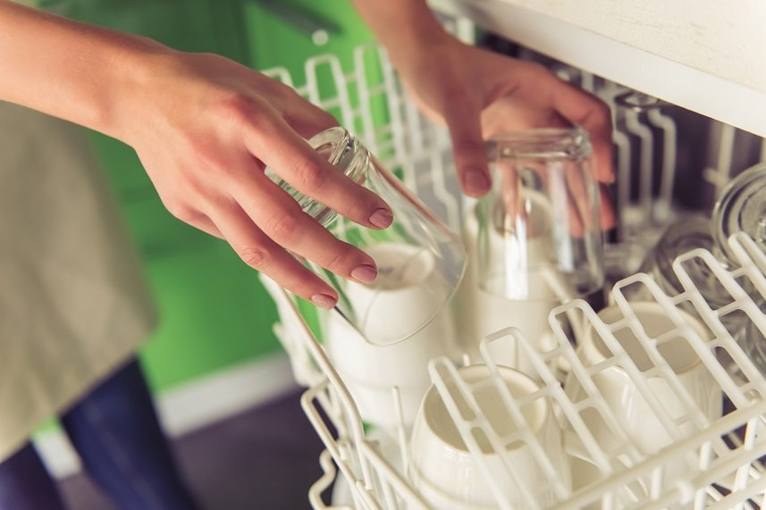 young woman putting dishes into dishwasher