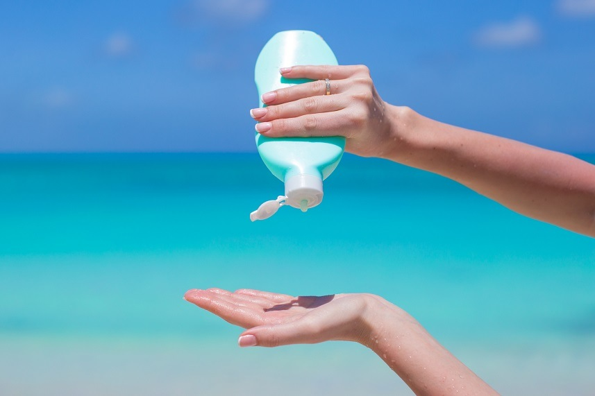 Woman hands putting sunscreen