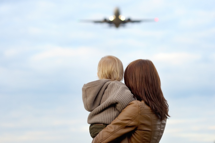 Young mother holding hes toddler son with airplane on background