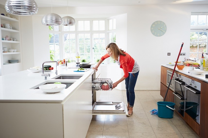 woman loading plates into the dishwasher