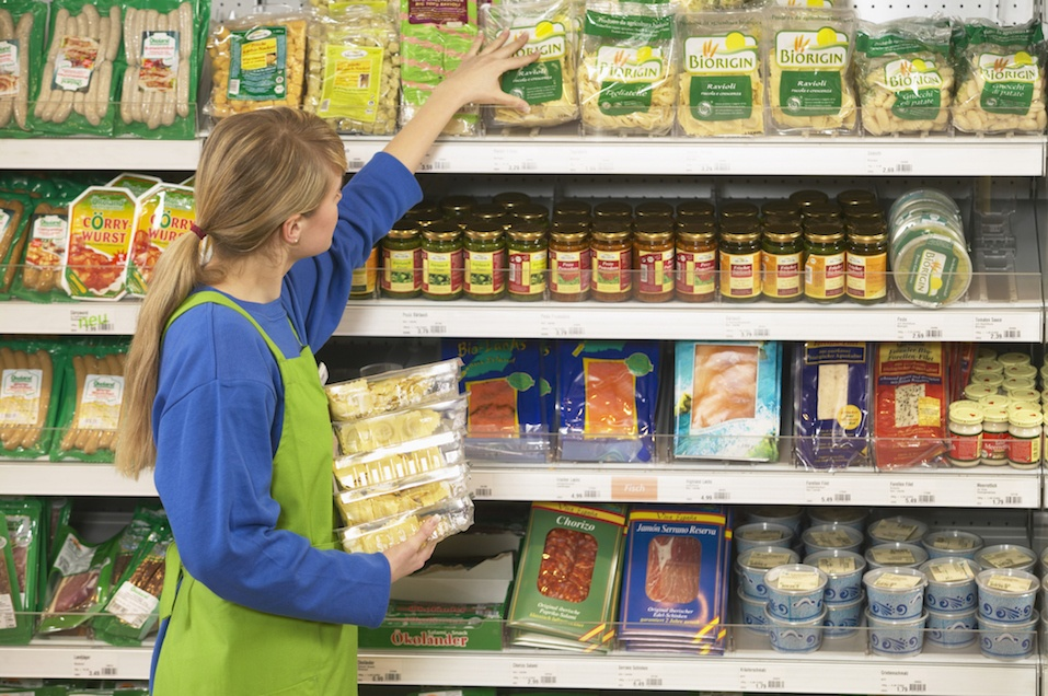 Woman stacking shelves in supermarket