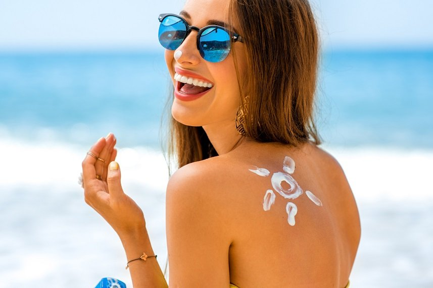 Young woman with sun shape in sunscreen on her shoulder