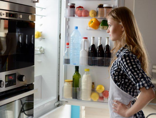 Woman with open refrigerator.