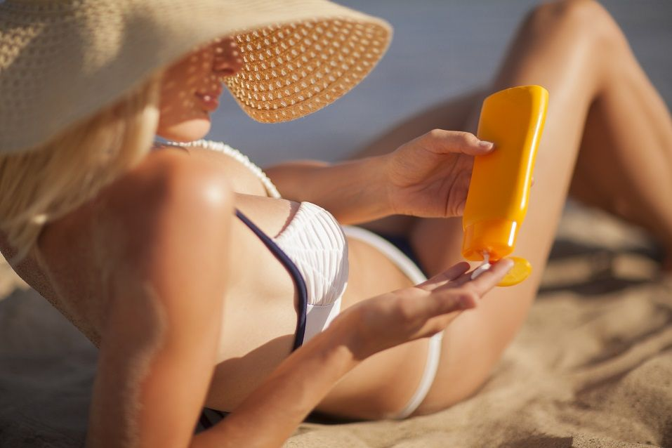 woman lying on the beach in the hat