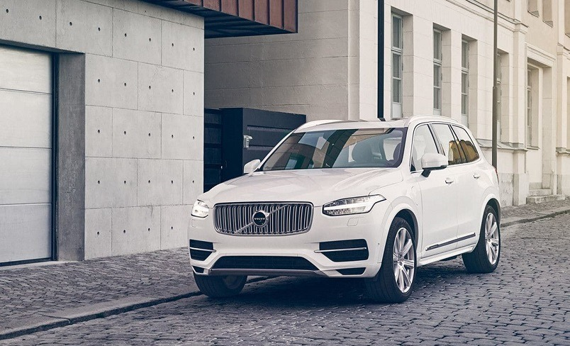Fron three quarter view of white Volvo XC90 outside a garage