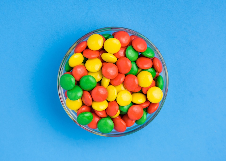 A bowl of yellow, green, and orange, hard chocolate covered candies.