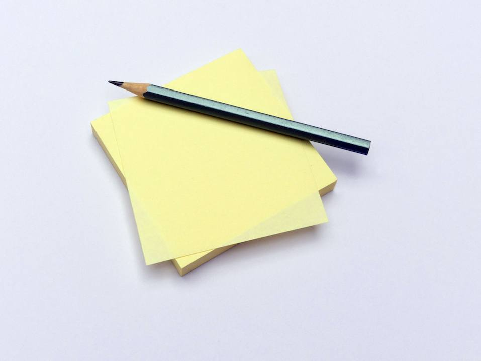 Yellow sticky notes and pencil