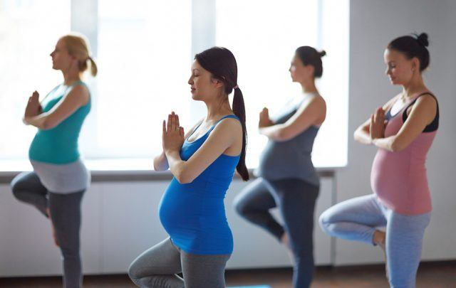 Young pregnant women doing yoga in gym.