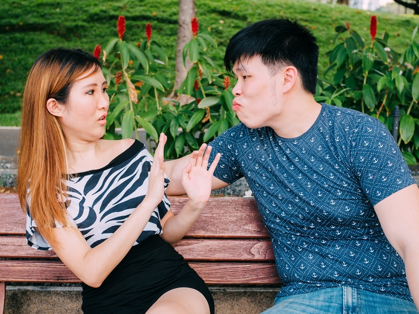 Asian man trying to kiss a girl