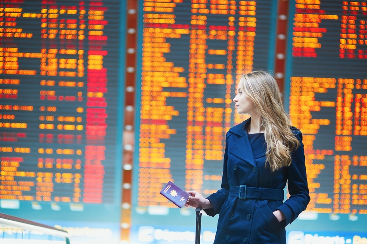 Young woman in international airport near the flight information board
