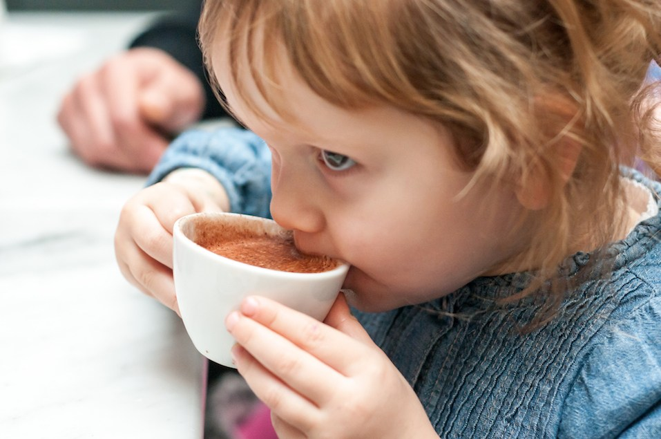 Young girl drinking a warm chocolate drink