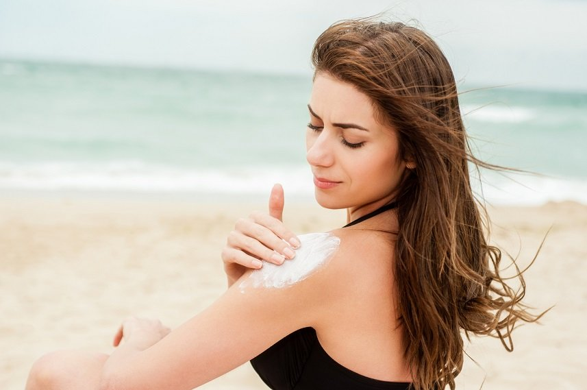 woman applying sunblock on the beach