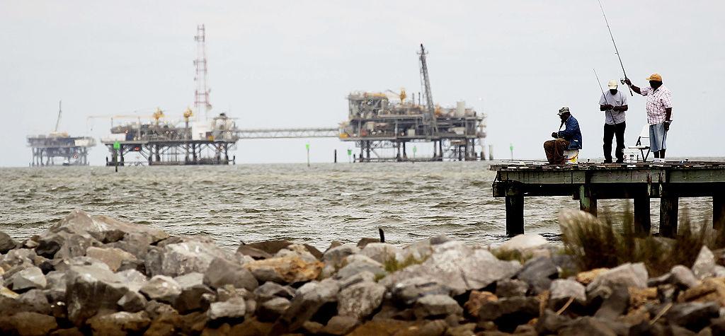 People fish near an oil rig on the Alabama coast